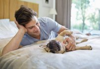 Man petting dog on bed at modern home — Stock Photo