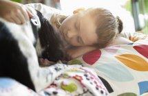 Посміхається дівчина ласки собаки на ліжку в сучасному будинку — стокове фото
