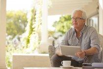 Homme souriant, à l'aide de tablette numérique sur la véranda — Photo de stock
