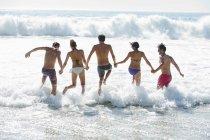 Друзья, взявшись за руки и плескались в океане — стоковое фото