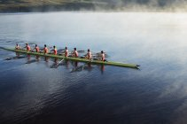 Rowing crew rowing scull on lake — Stock Photo