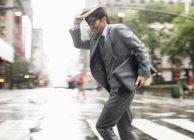 Uomo d'affari che attraversa la strada della città — Foto stock