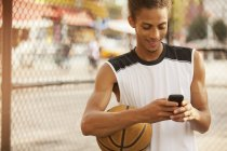 Man using cell phone on basketball court — Stock Photo