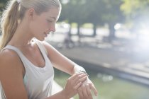 Woman looking at watch before exercising on city street — Stock Photo