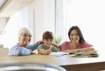 Tres generaciones de mujeres haciendo la tarea - foto de stock