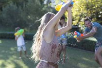 Family playing with water guns in backyard — Stock Photo