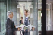 Бизнесмены пожимают руки в современном офисном здании — стоковое фото