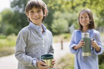 Children drinking from thermos outdoors — Stock Photo