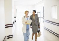 Doctor and businesswoman talking in hospital corridor — Stock Photo