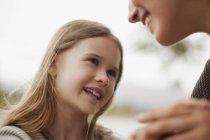 Primo piano di figlia sorridente guardando la madre — Foto stock