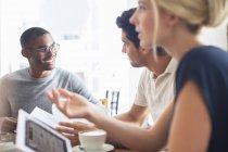 Les gens d'affaires parlent à une réunion dans un café — Photo de stock