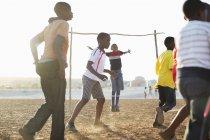 Niños africanos jugando al fútbol juntos en el campo de la suciedad - foto de stock