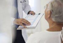 Médico mostrando historia clínica al paciente en la habitación del hospital - foto de stock