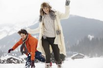 Playful couple running in snowy field — Stock Photo
