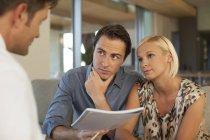 Conseiller financier, parler à couple sur canapé — Photo de stock