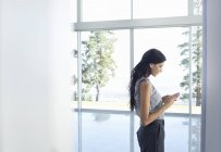Businesswoman using cell phone at window at modern office — Stock Photo