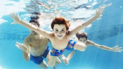Familie gemeinsam schwimmen unter Wasser im Pool — Stockfoto