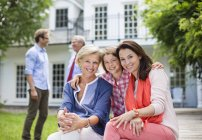 Family smiling together outside house — Stock Photo