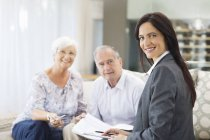 Financial advisor talking to couple on sofa — Stockfoto