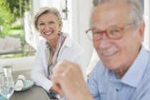 Paar lächelt gemeinsam am Tisch — Stockfoto