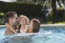 Familia jugando en la piscina - foto de stock