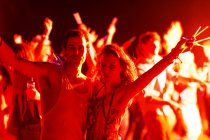Portrait of couple with glow sticks dancing at music festival — Stock Photo