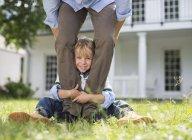 Мальчик выглядывает из-под ног отца. — стоковое фото
