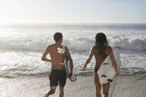 Couple running with surfboards toward ocean — Stock Photo