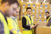 Businessman and workers in warehouse — Stock Photo