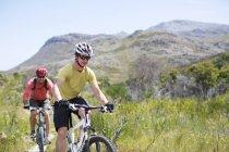 Two caucasian mountain bikers on dirt path — Stock Photo