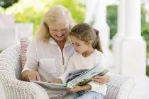 Anciana leyendo a nieta en porche - foto de stock