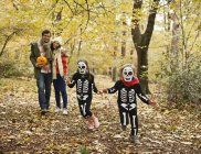 Crianças em trajes de esqueleto jogando no parque — Fotografia de Stock