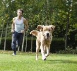 Man running together with dog in park — Stock Photo