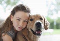 Detailansicht der Mädchen umarmt Hund drinnen — Stockfoto