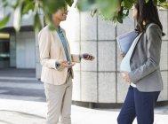 Dos mujeres de negocios felices hablando en la calle de la ciudad - foto de stock