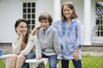 Mother and children smiling outdoors — Stock Photo