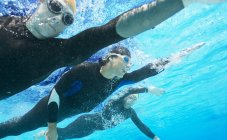 Confident and strong triathletes in wetsuits underwater — Stock Photo
