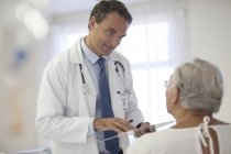 Doctor talking to older patient in hospital — Stock Photo