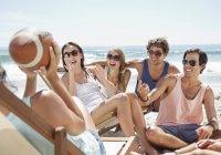Glückliche Freunde mit Fußball hängen am Strand — Stockfoto