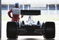 Гонщик стоит с машиной в гараже — стоковое фото