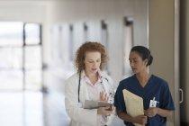 Врач и медсестра разговаривают в коридоре больницы — стоковое фото