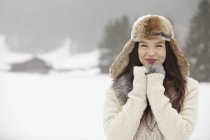 Portrait of smiling woman wearing fur hat and gloves in snowy field — Stock Photo