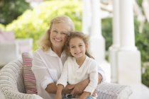 Older woman and granddaughter smiling on porch — Stockfoto