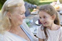 Mulher mais velha, sentada com a neta ao ar livre — Fotografia de Stock