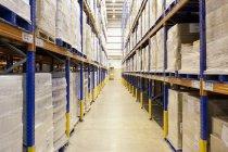 Piles de boîtes dans l'allée en entrepôt — Photo de stock