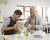 Young happy businessmen having breakfast together — Stock Photo