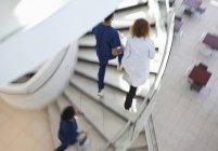 Hospital staff climbing spiral steps — Stock Photo