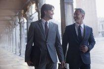 Uomo d'affari sorridente che cammina lungo il corridoio — Foto stock
