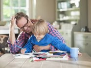 Father and son doing homework at kitchen table — Stock Photo
