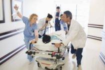Doctors rushing patient on gurney in hospital corridor — Stock Photo